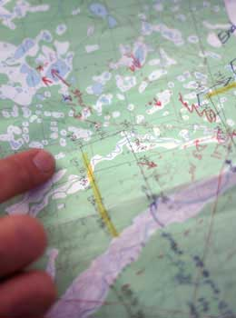 finger pointing at routes on map